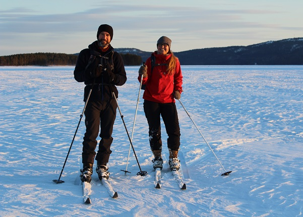 Image: Two persons skiing on forest skis on Lake Pielinen at sunset.