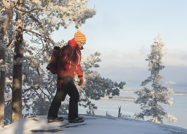 Image: Person walking with snowspikes in Koli hills.