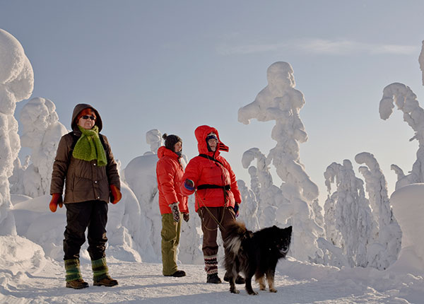 Image: People with a dog in winter forest in Koli National Park.